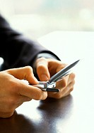 Hands of businessman using cell phone, close-up