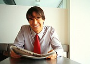 Businessman smiling at camera, holding newspaper, head and shoulders