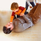 Children playing with father on the floor