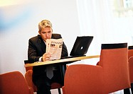 Businessman sitting reading paper