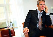 Businessman sitting, talking on cell phone (thumbnail)