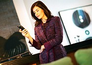 Businesswoman standing, holding cell phone, tilt