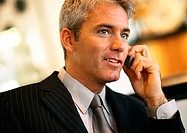 Businessman talking on cell phone, head and shoulders