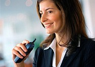 Businesswoman smiling, holding cell phone