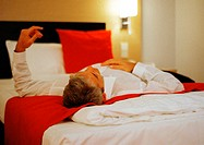 Businessman lying across bed