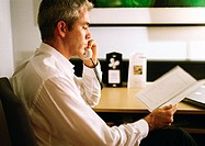 Businessman talking on phone, looking at paper, side view, close-up