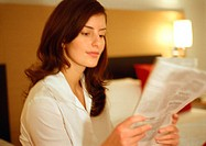 Businesswoman reading paper, head and shoulders, close-up, blurred