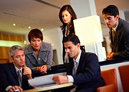 Group of business people, standing and sitting, looking at document, tilt