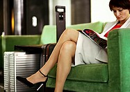 Businesswoman sitting in chair reading, legs crossed