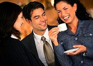 Businessman and businesswoman watching second businesswoman drink coffee, laughing