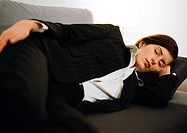 Businesswoman lying on couch, eyes closed
