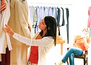 Woman looking at clothes in store, man watching behind her