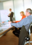 Business people sitting in meeting, blurred