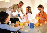 Family eating breakfast together, father pouring drinks
