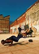 Man balancing on hands, break dancing in urban setting