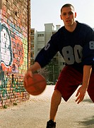 Man dribbling basketball in urban playground next to graffitied wall
