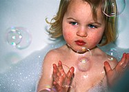 Little girl in bubble bath with bubbles in the air