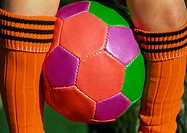 Soccerball between legs, close up