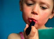 Little girl putting on lipstick, close-up