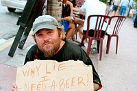 Vagrant holding sign ´Why lie I need a beer´. Ocean Drive. Miami Beach. Florida. USA