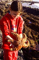 girl holding starfish at tide pools