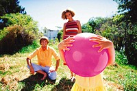 Girl holding ball with parents