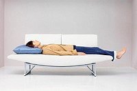 Man lying down on modern sofa