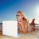 Woman with laptop computer on beach