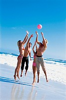 Group of friends playing with a ball on the beach