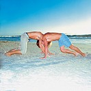 Men wrestling on the beach