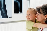 Girl and mother examining x-ray