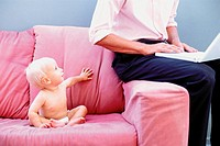 Baby on sofa with man typing