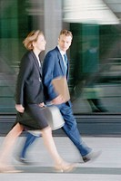Businessman and businesswoman walking briskly