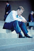 Businessman sitting on steps with cellphone