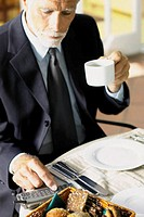 Businessman having breakfast with cellphone