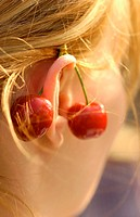 Woman with cherries behind ear