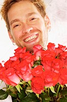 Smiling man holding red roses