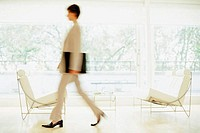 A businesswoman walking fast through trendy waiting room