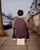 A young man sitting on a pile of books (thumbnail)