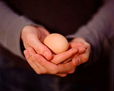 Young man carefully holding an egg (thumbnail)