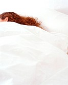 A woman sleeping in a cosy bed