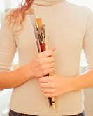 Woman holding paint brushes