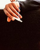 A person holding a lit cigarette
