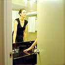 Woman looking in bathroom mirror