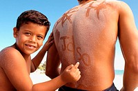 Boy writing on dad's sandy back