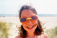 Girl on the beach with swimming goggles
