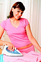 Young woman happily ironing