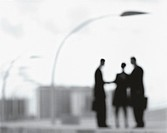Silhouettes of Business People Standing Below a Streetlamp