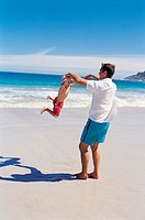 Father Swinging His Son By the Hands on the Beach