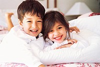Portrait of a Smiling Brother and Sister Lying in Bed